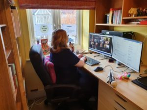 Amy sat in her home office space with 2 screens in front of her